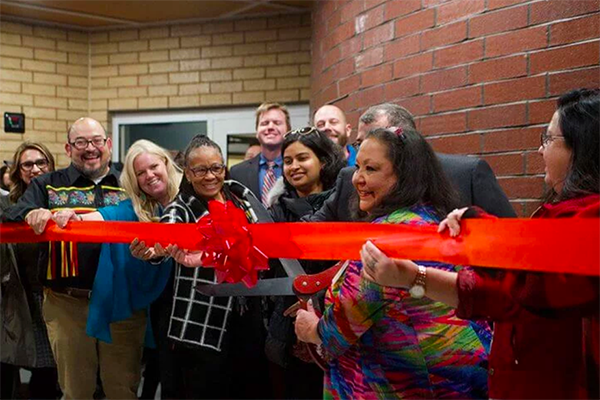 group of people celebrating a business opening by cutting a ribbon