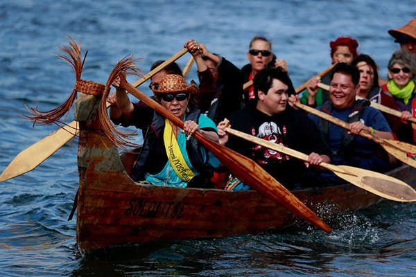 group of people paddling in a canoe