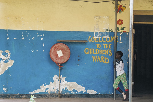 child in front of welcme to the childrens' ward message painted on wall